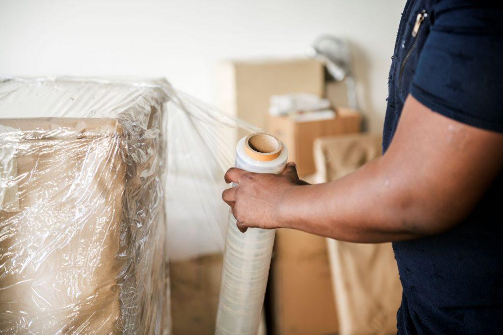 homme qui emballe des boites avec film plastique
