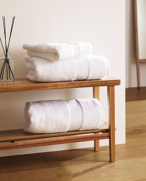 trois serviettes de spa blanche sur un banc en bois