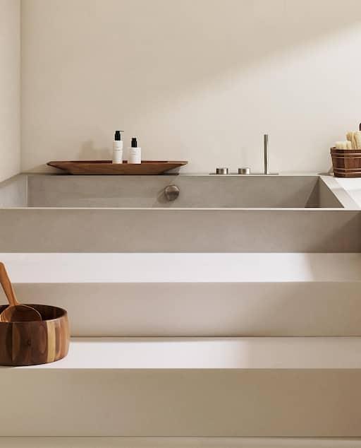 baignoire grise avec une marche et des accessoires en bois